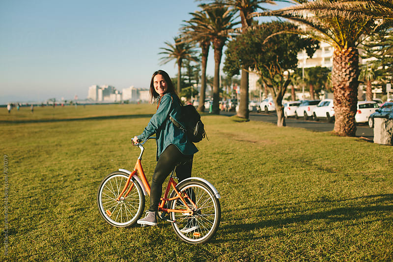 Beautiful girl riding her orange bicycle on the grass close to palm trees on the boulevard by Jonathan Caramanus for Stocksy United