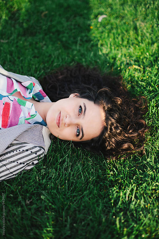 Beautiful woman lying on grass  by VeaVea for Stocksy United