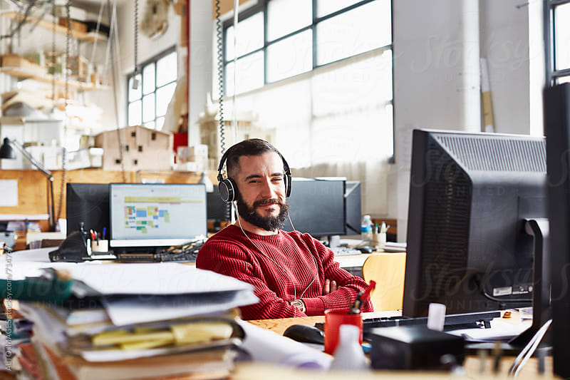 Happy Businessman Wearing Headphones In Office by ALTO IMAGES for Stocksy United
