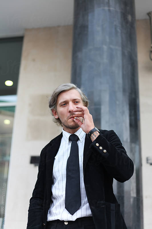 Stylish businessman smoking cigarette outdoors by Marija Mandic for Stocksy United