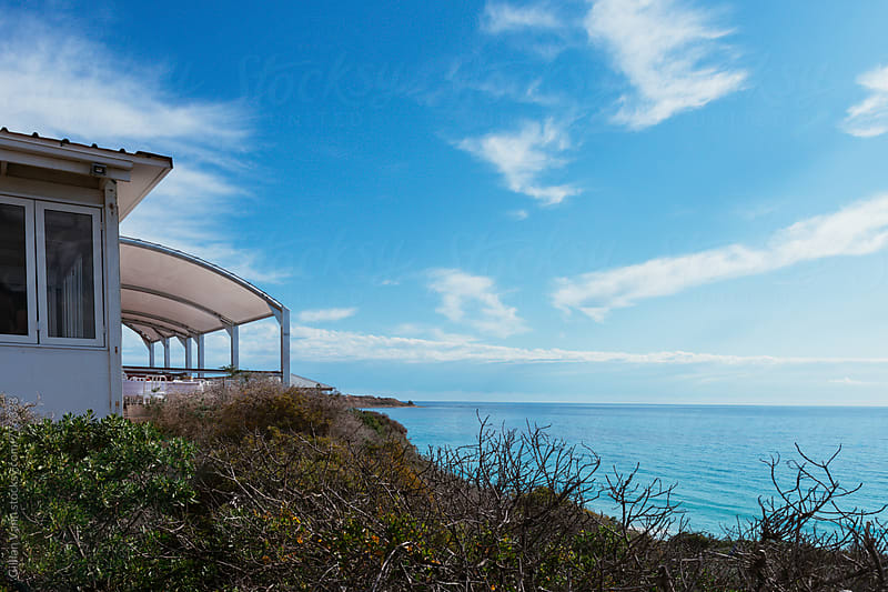 a restaurant sits on the cliff overlooking the beach by Gillian Vann for Stocksy United