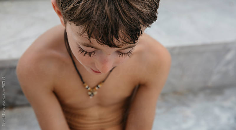 Closeup of a boy looking down, captured from above by Beatrix Boros for Stocksy United