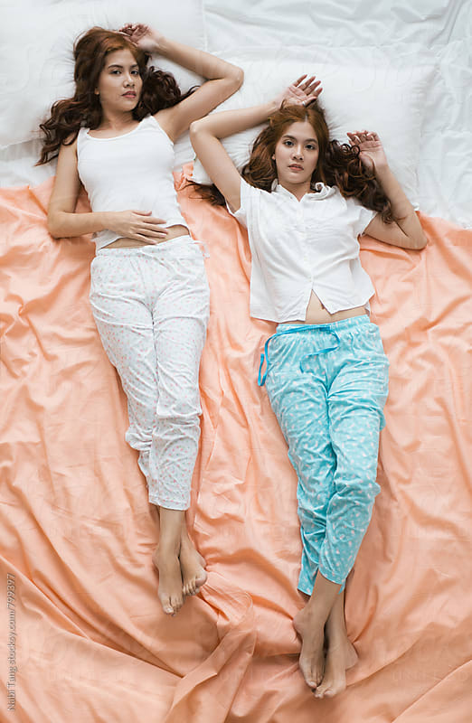 Beautiful Asian twin sisters on the pastel bed sheet by Nabi Tang for Stocksy United