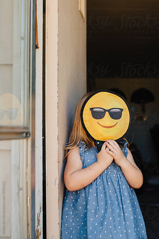 Toddler girl with a happy smiley emoticon face in front of her face. by Jessica Byrum for Stocksy United