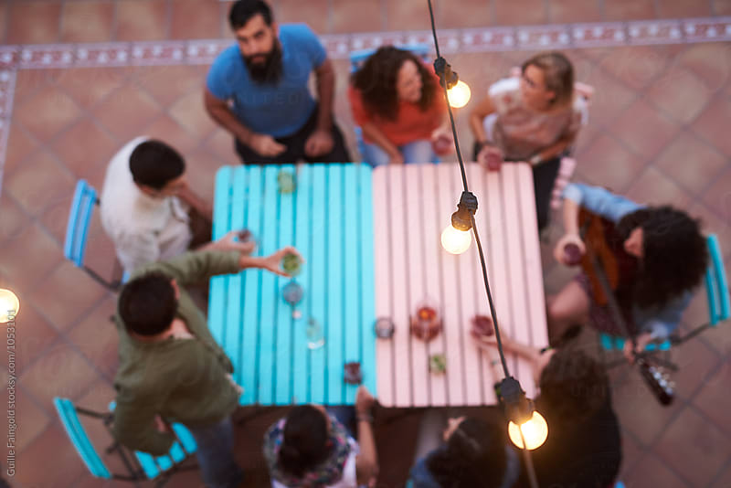 Focused garland above friends at table on backyard by Guille Faingold for Stocksy United