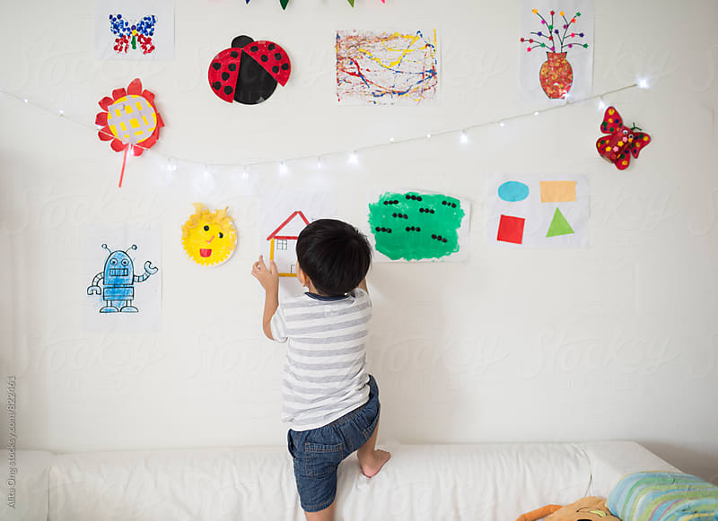 Little boy hang up his artwork on the wall by Alita Ong for Stocksy United