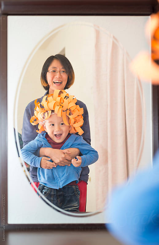Mother dressing her kid by funny crafts on head in mirror by Lawren Lu for Stocksy United