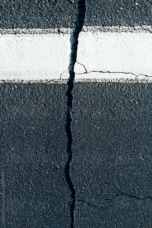 Crack in road and white boundary mark by Paul Edmondson for Stocksy United