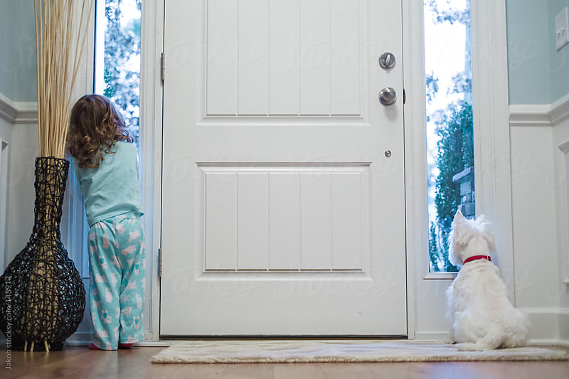 A white dog and young girl waiting for mom to come home from work.  by Jakob for Stocksy United