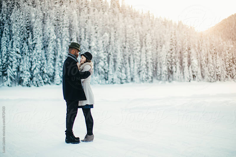 Mixed race couple in love holding each other on snow covered lake by Luke Liable for Stocksy United
