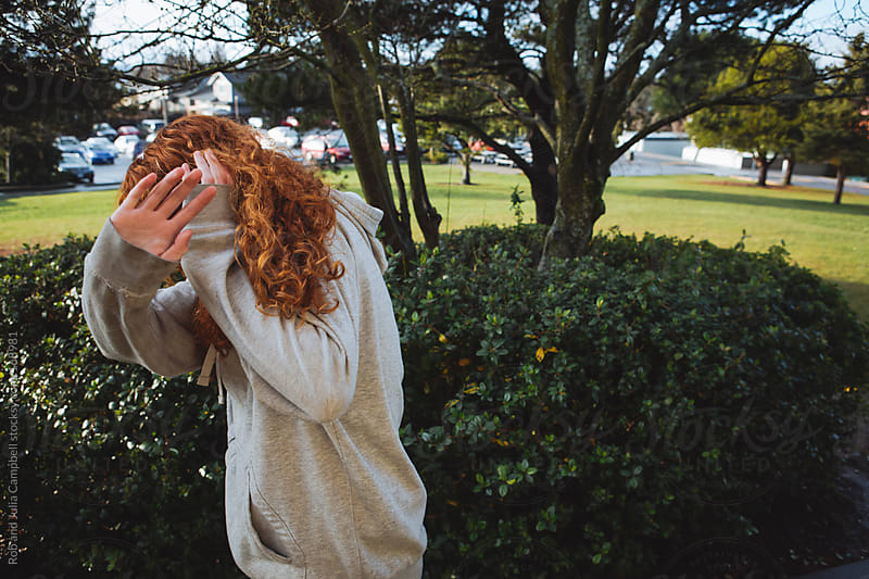 redhead teenage girl hides from camera by Rob and Julia Campbell for Stocksy United