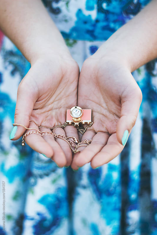Young woman holding little camera necklace in her hands by Jovana Rikalo for Stocksy United