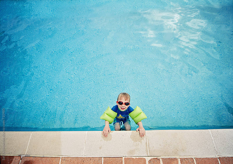 Little boy in a swimming pool by sally anscombe for Stocksy United