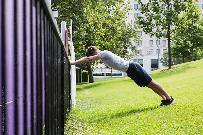 Sporty man doing stretching at the park by Mauro Grigollo for Stocksy United