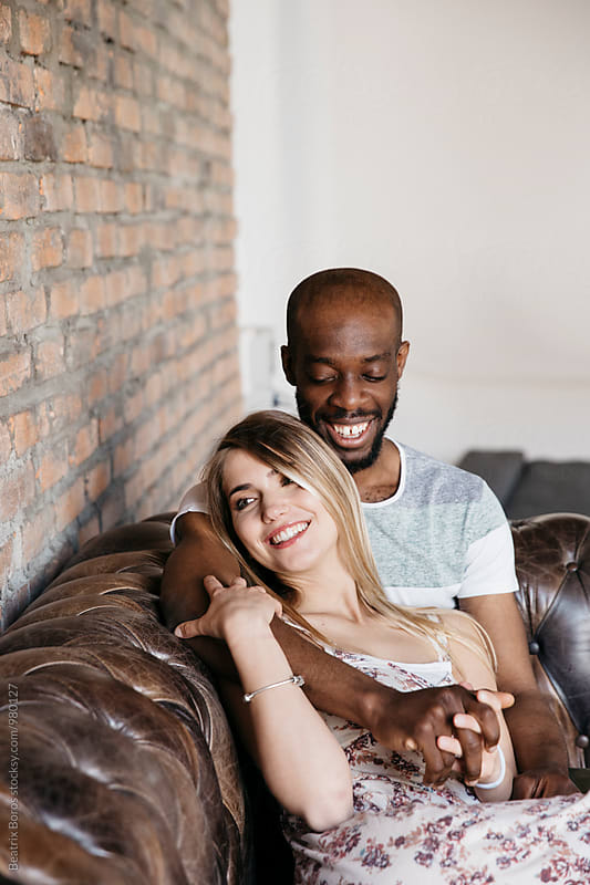 Intercultural couple having fun and laughing together on a leather couch by Beatrix Boros for Stocksy United