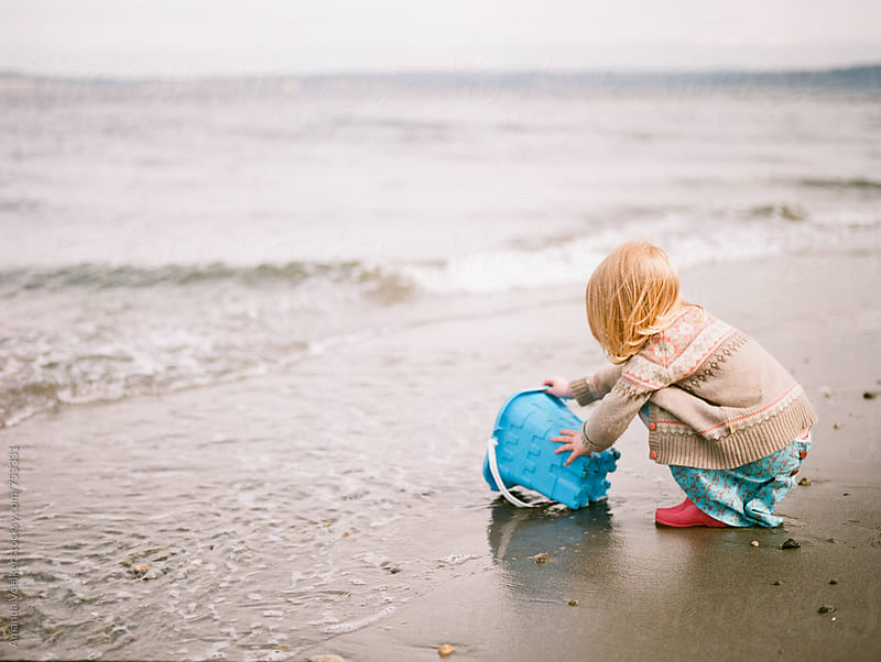 Little Girl at the Sea Shore Catches water in a Bucket by Amanda Voelker for Stocksy United