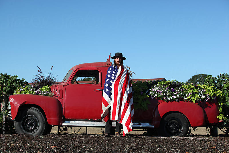 Americana Portrait Of A Cowboy Infront Of A Vintage Truck Wrapped In An American Flag by Carey Haider for Stocksy United