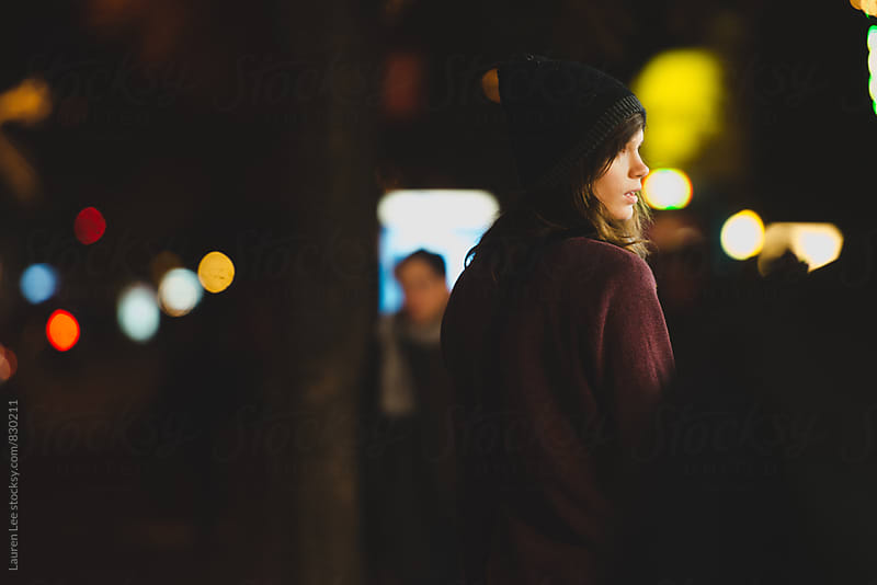 Woman walking alone at night by Lauren Naefe for Stocksy United
