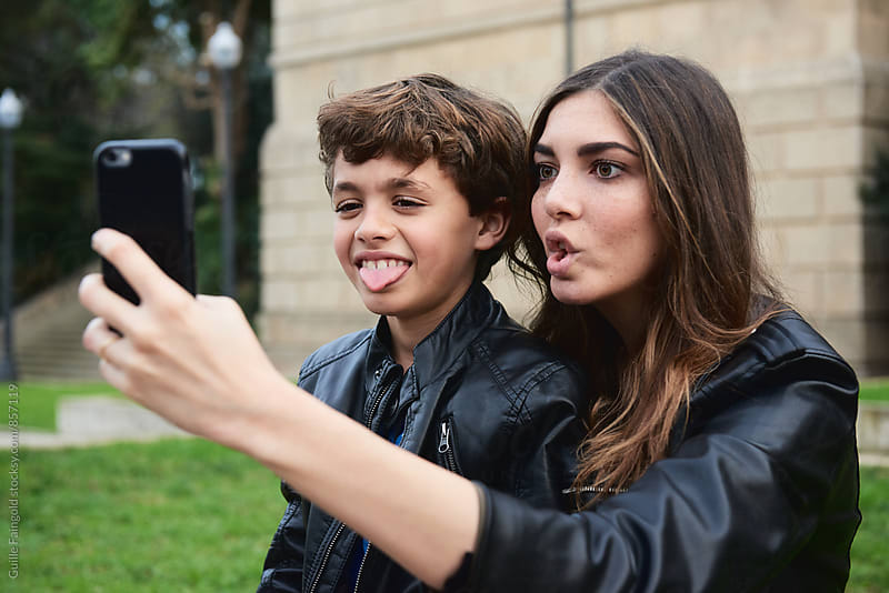 Sister and brother making face while taking selfie by Guille Faingold for Stocksy United
