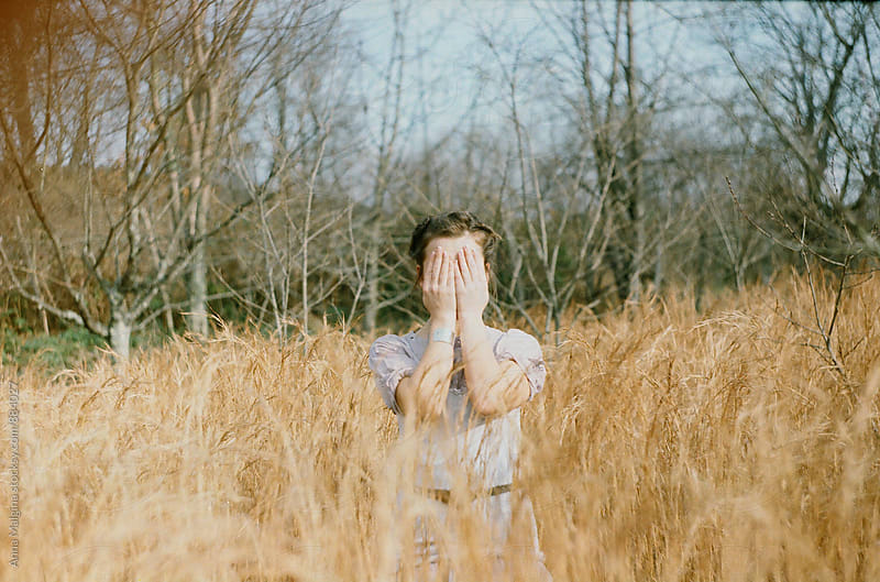 A film portrait of a young beautiful woman closing her eyes in the grass by Anna Malgina for Stocksy United