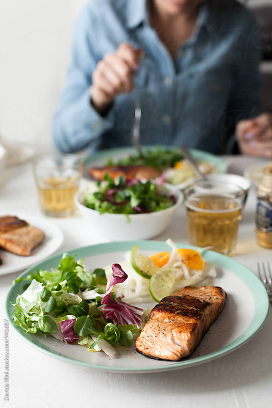 Woman eats a salmon fillet with mixed salad by Davide Illini for Stocksy United