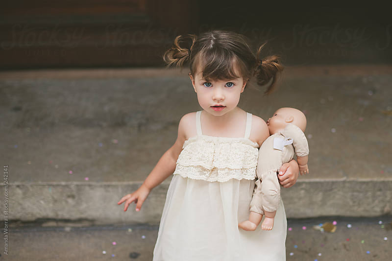 Beautiful toddler holding a baby doll, looking at camera by Amanda Worrall for Stocksy United