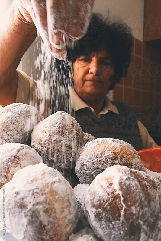 Senior woman in kitchen pouring shugar over donuts  by Dimitrije Tanaskovic for Stocksy United