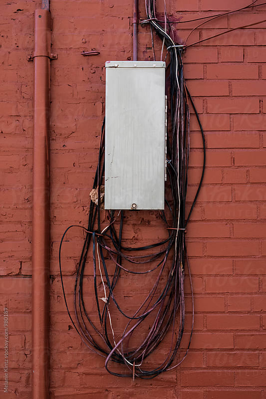 Connector box with cables on brick wall by Melanie Kintz for Stocksy United