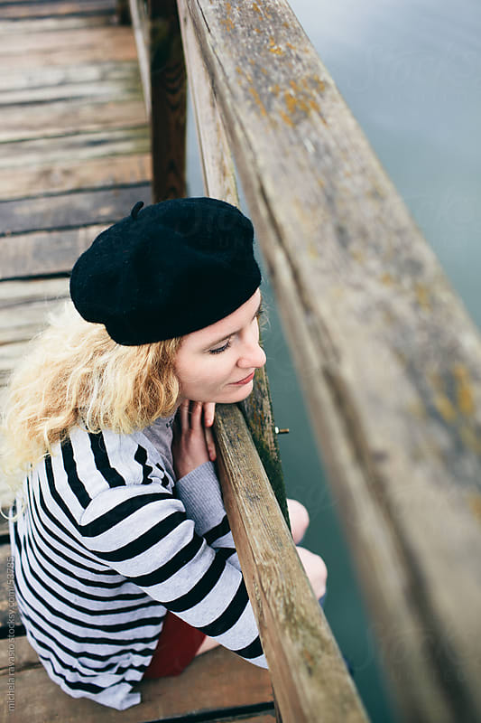 Young woman sitting on wooden river pier by michela ravasio for Stocksy United