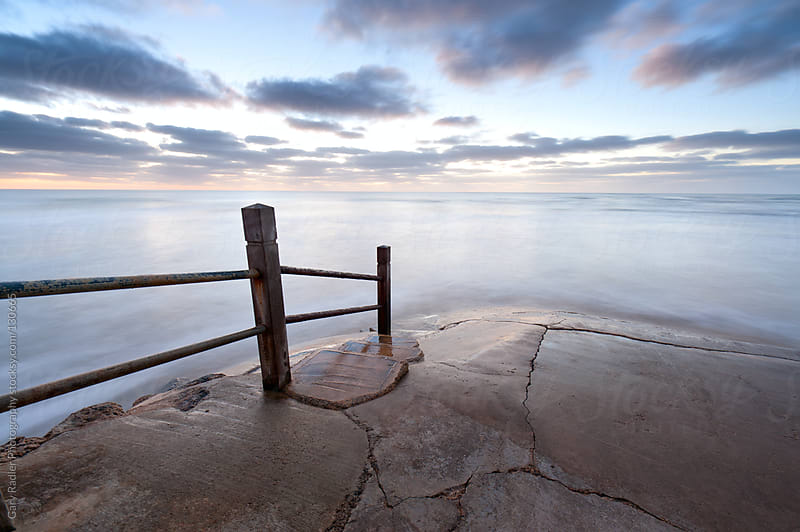 Handrail leading down into a Smooth Sea by Gary Radler Photography for Stocksy United
