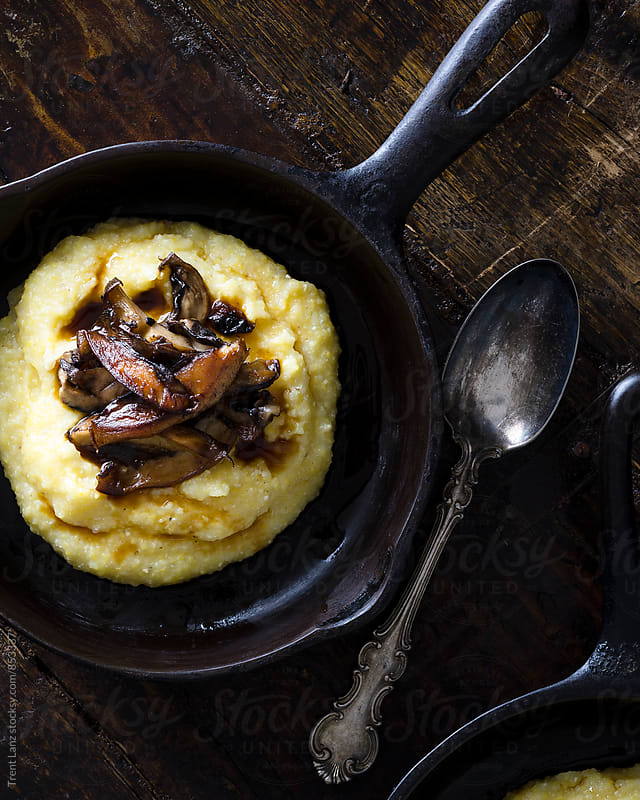 Mushroom polenta on a dark surface by Trent Lanz for Stocksy United