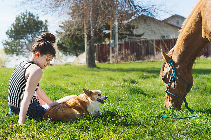 young woman sits with dog and grazing horse by Tana Teel for Stocksy United