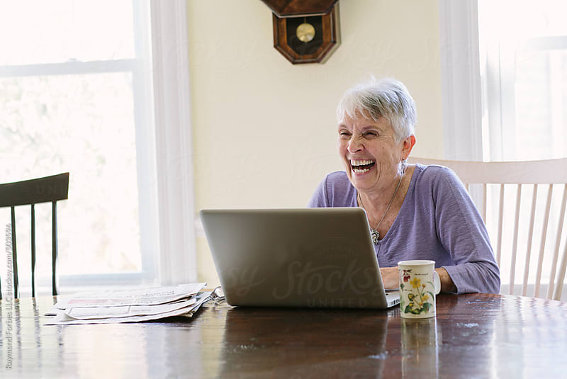 Senior Woman At Home working on Laptop by Raymond Forbes LLC for Stocksy United