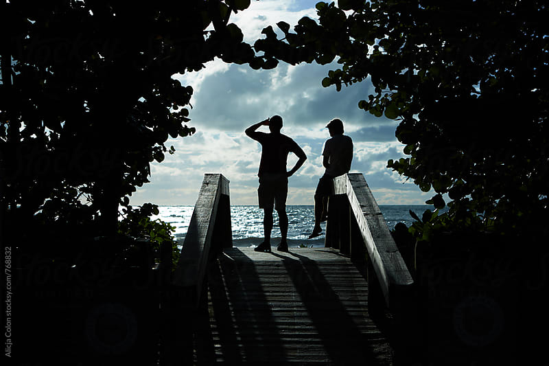 Two men gazing out to the beach by Alicja Colon for Stocksy United
