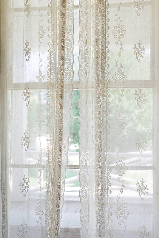 Delicate lace curtains covering a window in summer by Amanda Worrall for Stocksy United