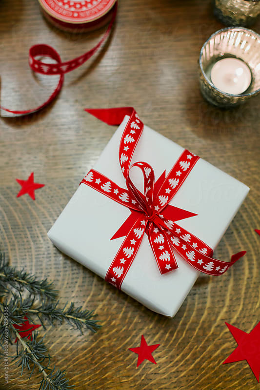 Overhead shot of gift wrapped with white paper and Christmas tree patterned ribbon by Laura Stolfi for Stocksy United