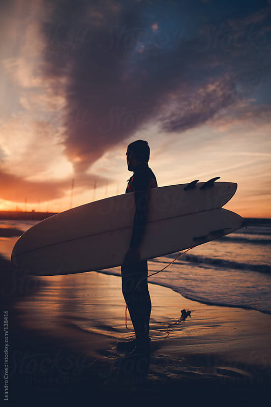 Unrecognizable surfer with board on sunrise by Leandro Crespi for Stocksy United