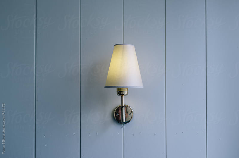 Vintage wall lamp with wooden background by Tomas Mikula for Stocksy United