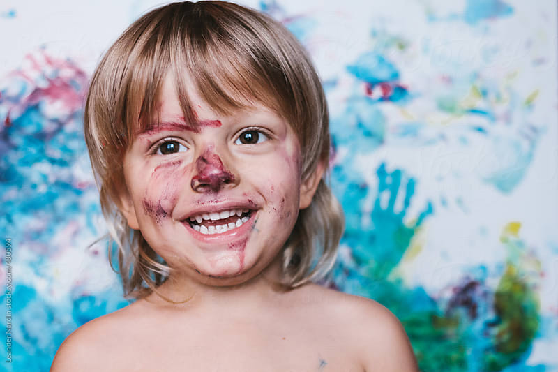 portrait of a smiling colorfully painted toddler by Leander Nardin for Stocksy United