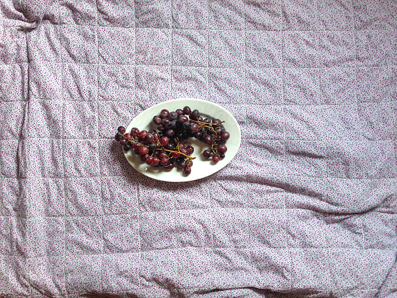 Grapes in a white bowl - from above, horizontal by Marija Kovac for Stocksy United