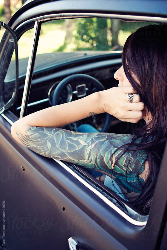 Woman with arm tatto sleeve sitting in vintage car. by Tana Teel for Stocksy United