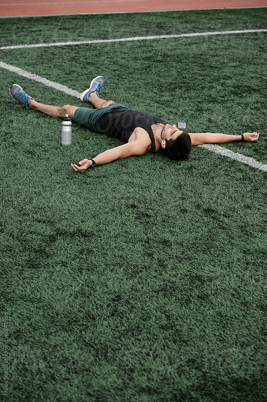 Sportsman laying on grass by Milles Studio for Stocksy United