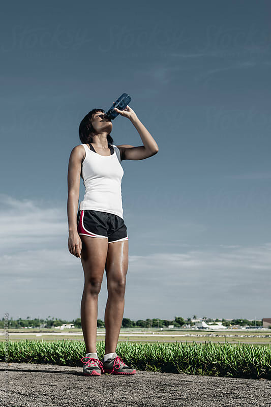 Woman Runner Drinking Water by Stephen Morris for Stocksy United