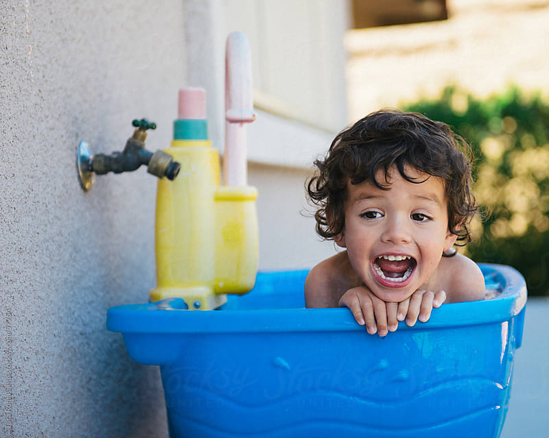 toddler boy plays in a water table by Tara Romasanta for Stocksy United