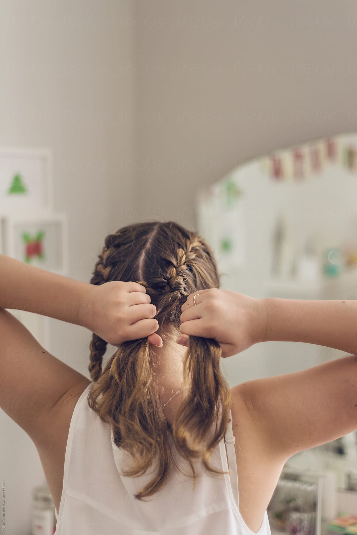 5d102a60b1a1 teen girl braiding her hair by Gillian Vann for Stocksy United
