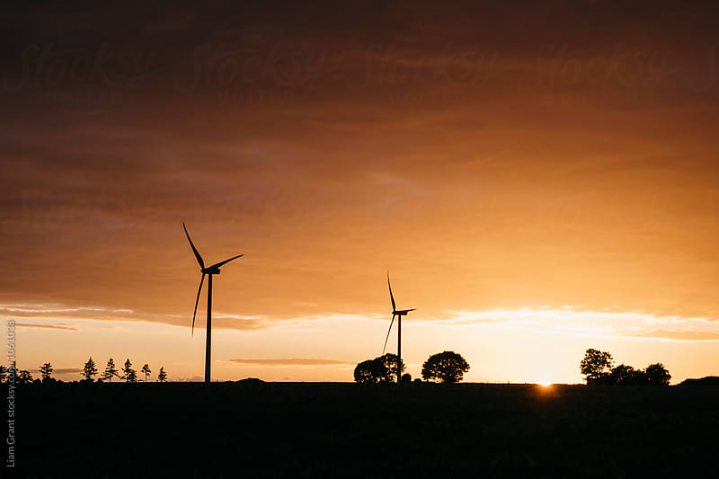 Wind turbine silhouetted against orange cloud at sunset. Norfolk, UK. by Liam Grant for Stocksy United