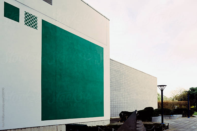 Two modern commercial buildings, one with a large green square for decoration by Paul Phillips for Stocksy United