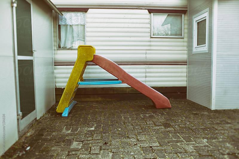 Old plastic slide in trailer park by Marcel for Stocksy United
