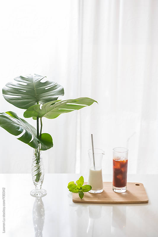 Delicious milk tea and fresh leaves in vase on table. by Lawren Lu for Stocksy United