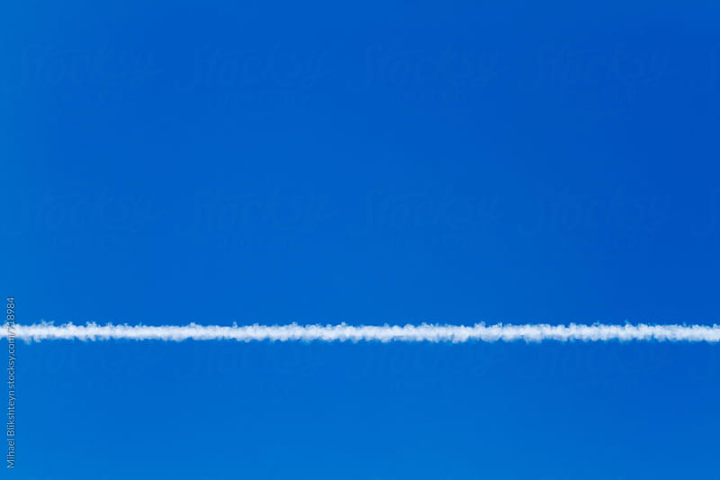White contrail against blue sky on a sunny day looking up by Mihael Blikshteyn for Stocksy United